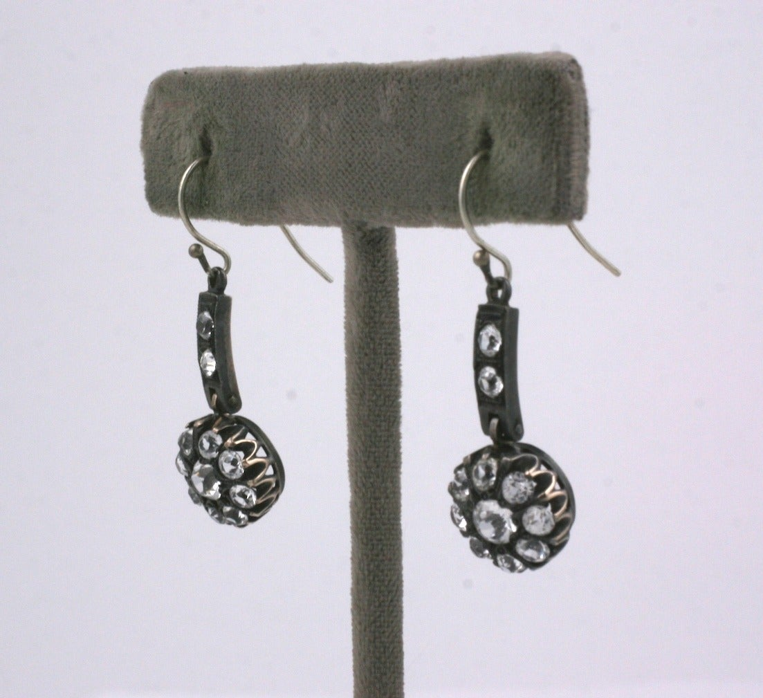 Antique paste articulated earrings are set in sterling silver from the late 19th Century. The pastes on the cluster drop are set into crown settings and are suspended from a paste set bar. 1