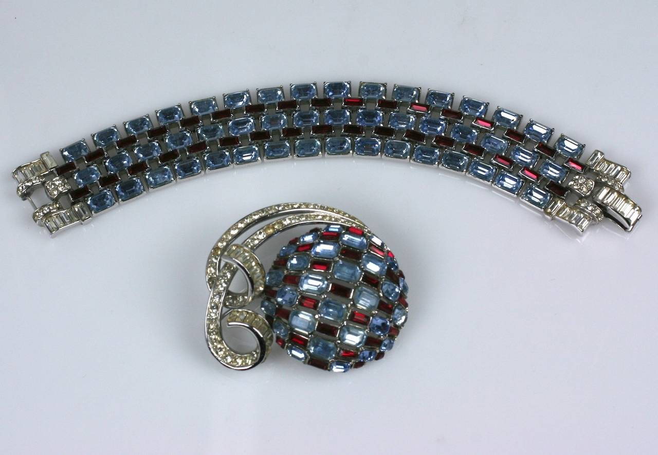 Trifari Art Deco Suite in faux aquamarine and rubies in high Art Deco style. Emerald cut faux aquas are mixed with faux ruby baguettes and pave accents to form the elegant bracelet and domed brooch with pave swirl decoration.  Bracelet 7