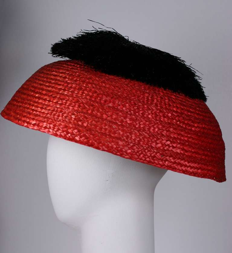 An antique Chinese Court Hat inspires Italian high fashion. Rendered in bright red straw with an oversized pom pom of fine black raffia. Elegant Italian 1950's resort fashion. Excellent condition. 1950's Italy.