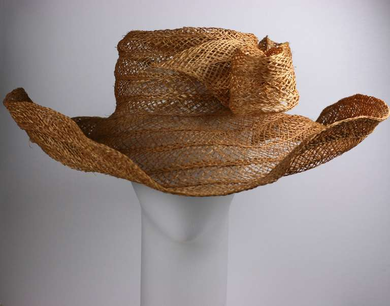 Massive handwoven openwork straw hat with large bow. This scale of this picture hat is incredibly striking and editorial. Insane and rumpled in a good way. 