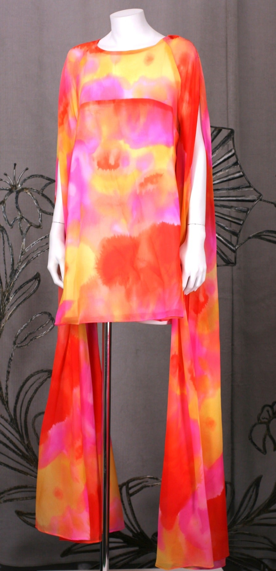 Unusual mini dress with elongated tubular flared sleeves and vibrant, sheer watercolor print. Dress is lined from bust down, the top bodice and sleeves are sheer.  Long sleeves are slashed for movement. Back Zip entry. 1960's USA. Very Good