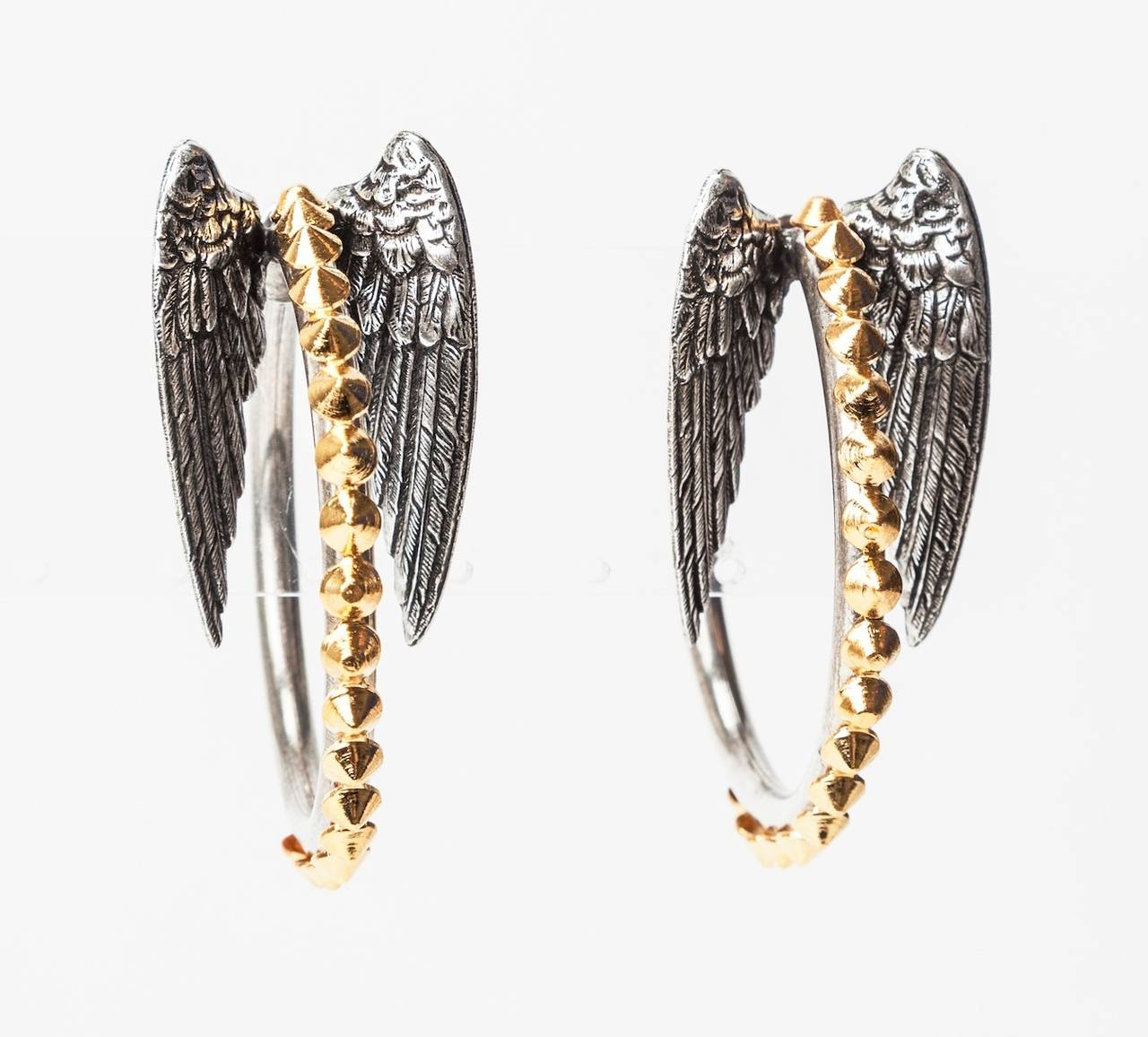 Oversized hoop earrings with wings on ears. Antique silver toned metal with gold stud applications. Made in the Parisian studios of Mark Walsh Leslie Chin.