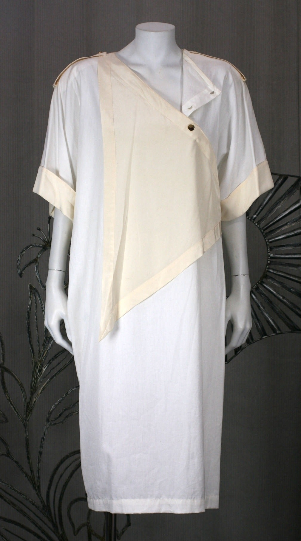 Genny's cotton poplin summer dress with cream silk crepe de chine scarf panel and trim by Gianni Versace. Straight cut dress falls from large shoulder pads. Assymetric neckline opens with hidden snaps. 1980's Italy. Excellent condition.