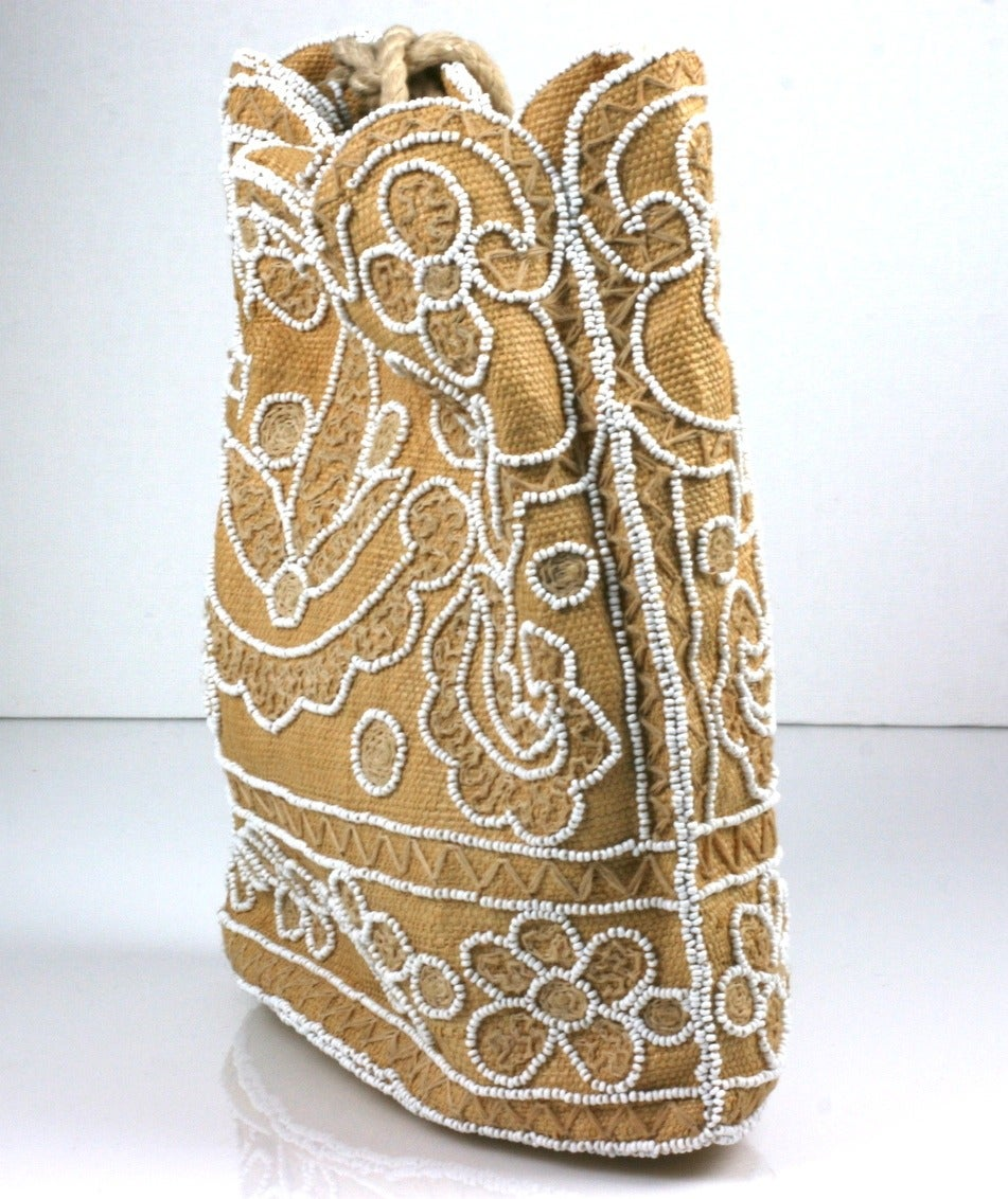 """Chalk Beaded Raffia Bag with drawstring ties. Floral patterns embroidered with natural raffia thread and outlined in chalk glass beads throughout. France 1950's.  9"""" x 9"""" x 3"""". Excellent condtion."""