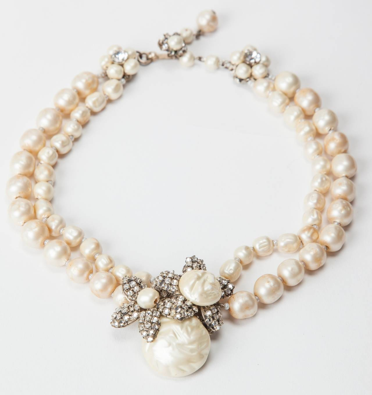 Miriam Haskell Classic two strand signature freshwater faux pearl necklace of silver gilt with a centerpiece of vari sized baroque button pearls and hand sewn crystal rose monte flowers. Adjustable classic hook and pearl chain closure.  14-16