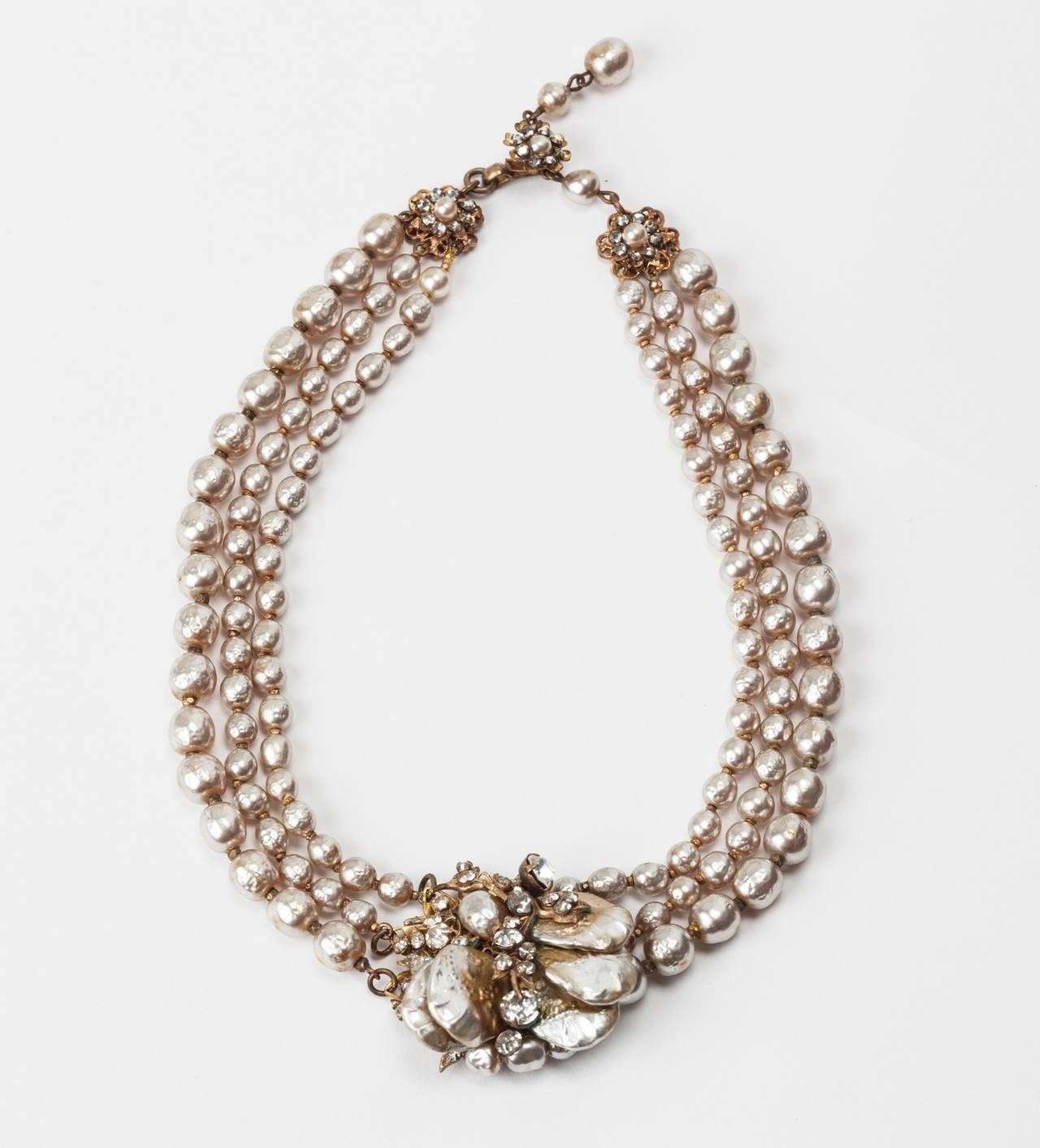 Miriam Haskell Classic three strand (three size) signature baroque faux pearl necklace. The center motif is made of Miriam Haskell's classic signature Russian gilt filigrees and crystal pastes. Vari sized baroque pearl petals with round and oval