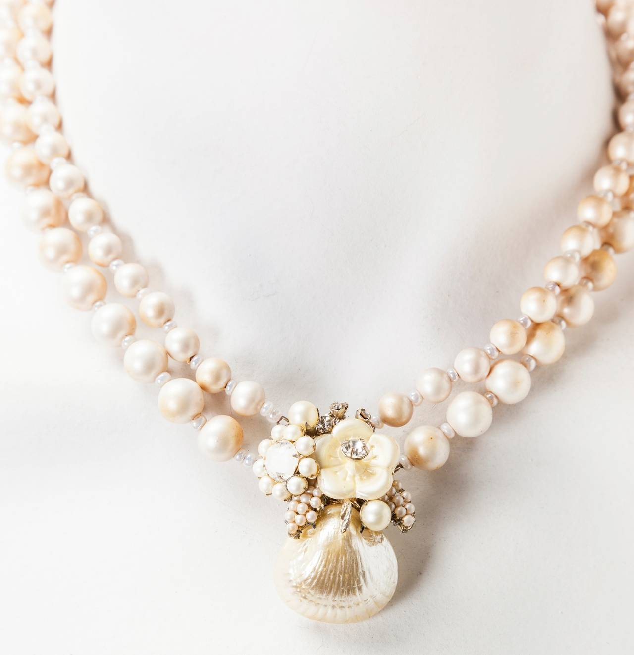 Miriam Haskell's signature freshwater pearl two strand necklace. The double strand faux pearl beads are separated with white pate de verre spacers. A center clasp of a nacre laquered glass scallop shell is further decorated with floral motifs and