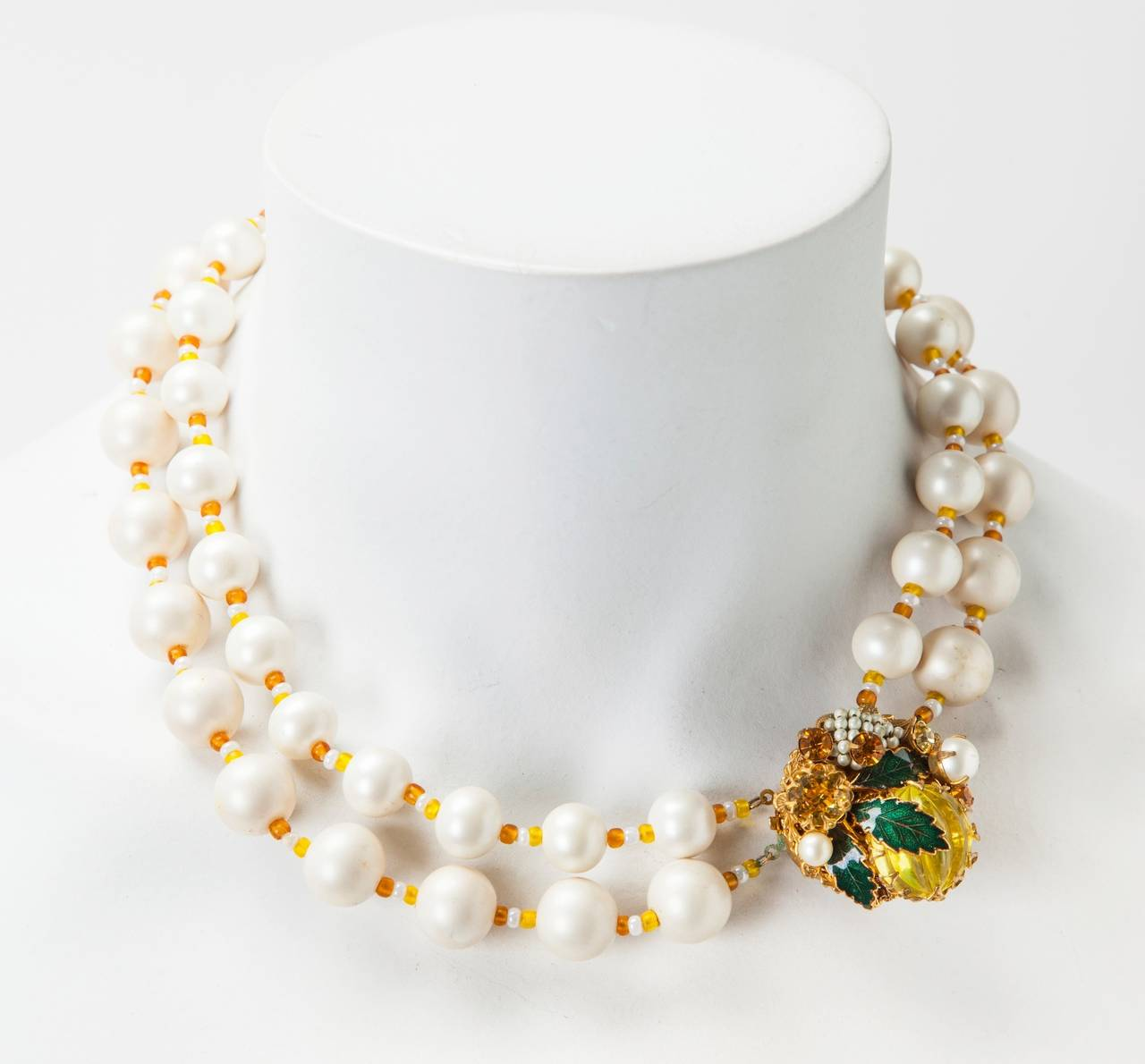 Miriam Haskell's Signature freshwater faux pearl double strand necklace.The two varying size strands are spaced with topaz and white pate de verre seed beads.The elaborate clasp is embellished with emerald green enamel leaves, faceted prong set
