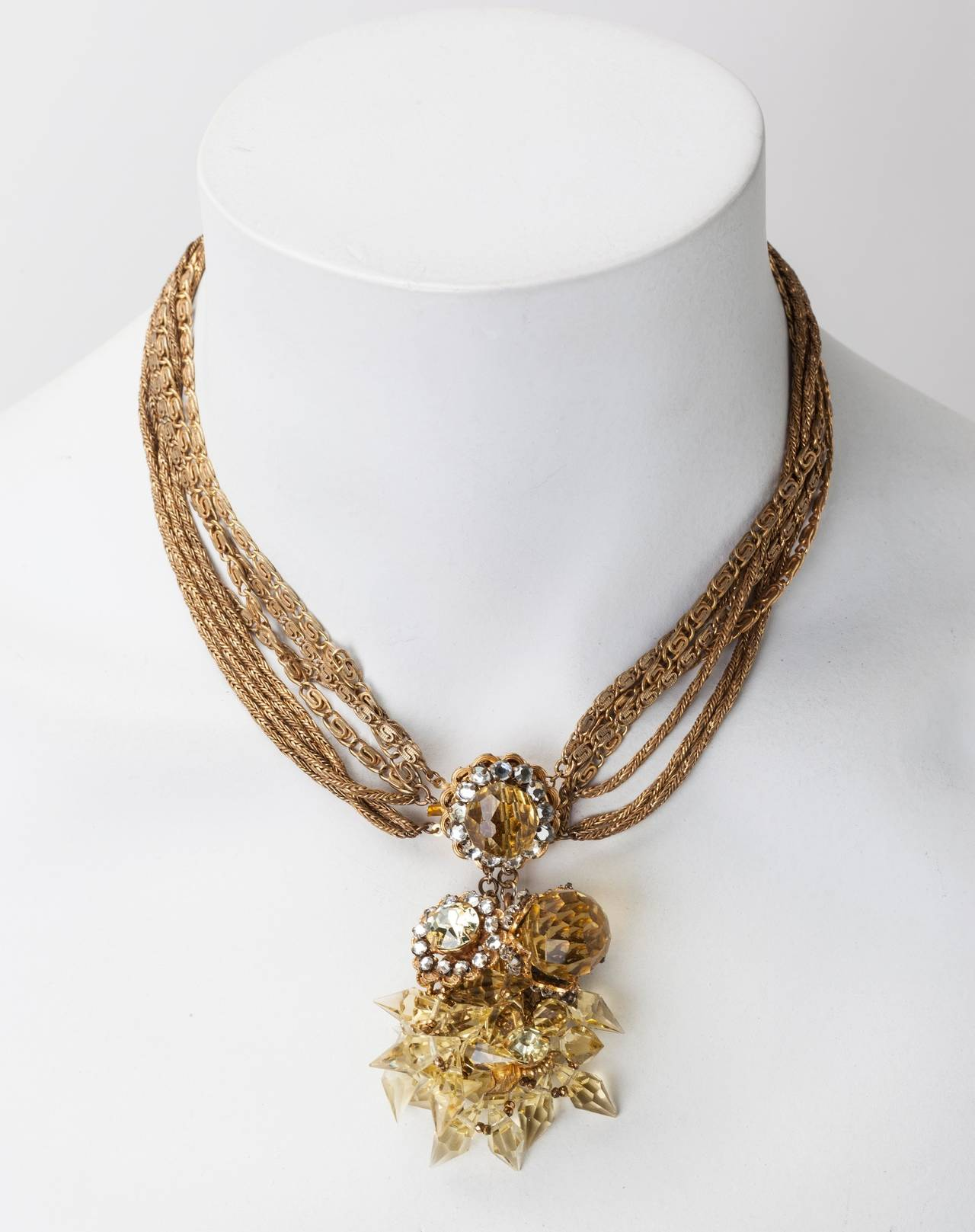 Miriam Haskell signature Russian Gilt, multi strand chain necklace with large central pendant clasp of faceted faux citrine round and pointed crystals. The clasp is further embellished with hand sewn crystal rose montes, and tiny gold cut steel