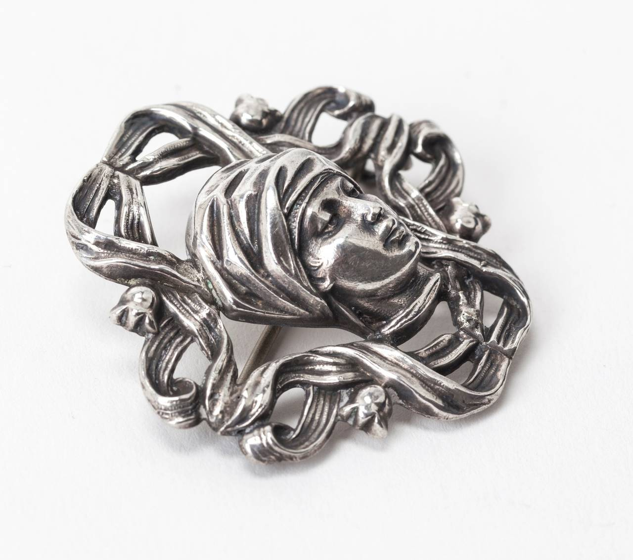 Art Nouveau sterling high relief brooch of a maiden with head wrap. Whiplash ribbons of silver form the frame capped in tiny lily of the valley buds. Highly unusual subject matter. Most Art Nouveau material is more romantic and feminine as opposed