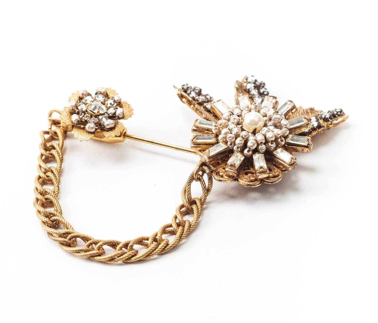 Miriam Haskell's two part stickpin brooch of Signature Russian Gilt with hand sewn, crystal rose monte leaves and crystal and faux baroque pearl flower heads. These are connected to the closure by a textured Russian Gilt chain safety chain which