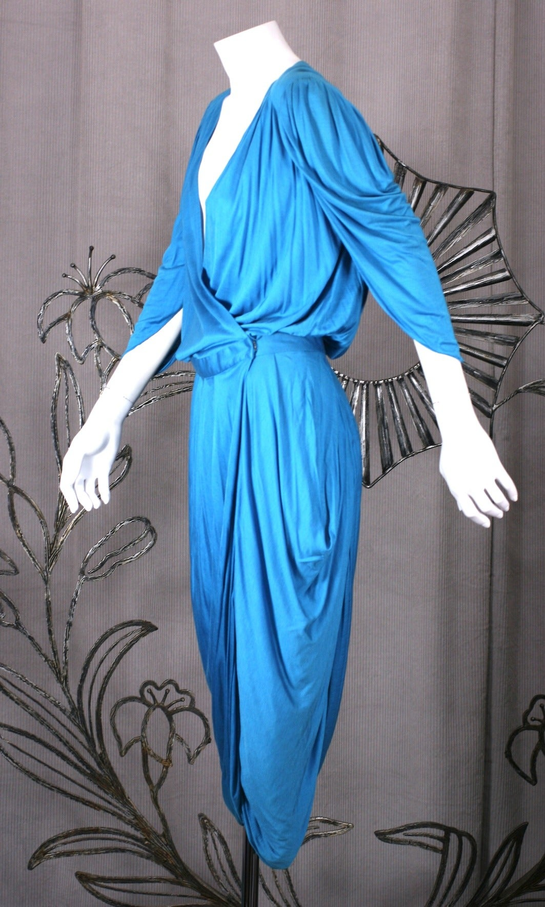Helga Howie's sexy silk blend jersey draped wrap dress with a split, pegged skirt like a pair of beetle wings. Sleeves and hips are draped as well. The tucks (which create the drape) are held by a fixed waistband that fastens to the left side (and
