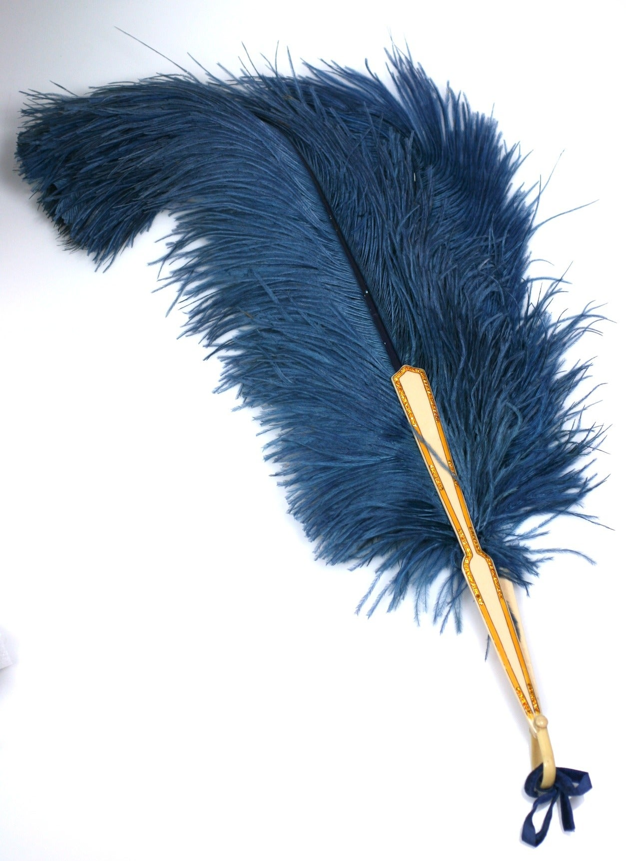 """Celluloid Flapper Fan with deep blue ostrich feathers. This fan does not """"open"""" but remains in one flirtatious position, as shown. The celluloid stems are detailed with over painting and set with citrine pastes. 22"""" x 5"""" at top. 1920's France."""