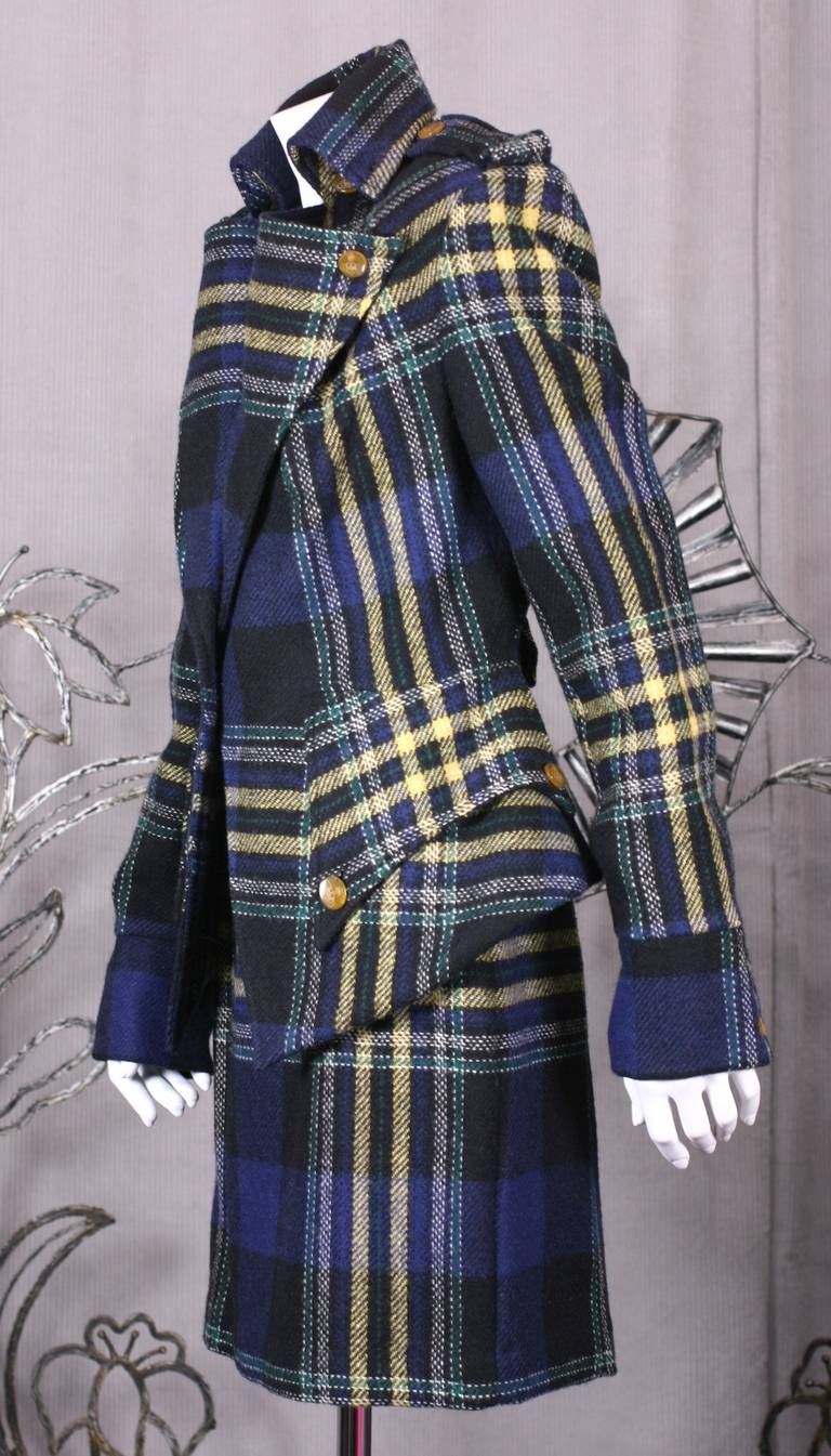 Vivienne Westwood English tweed suit with oversized shoulders, epaulets, collar, revers and peplum. Great dip front hem jacket wearable as separate. Oversized flaps cover pockets at nipped waist and martingale half belt releases pleats over center