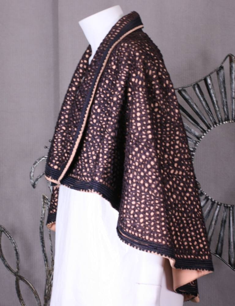 Unusual soutache ribbon embroidered capelet from the 1940's with a vaguely Victorian feeling. The flowing capelet is cut in fleshy pink wool gabardine with swirls of navy and black ribbon trim and corded edging throughout. Large shawl collar is