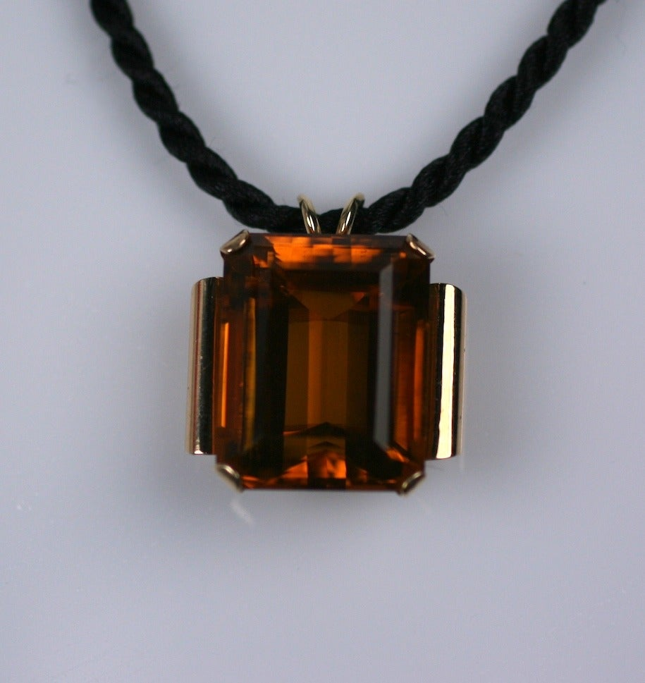 Retro pendant set in heavy 14k gold with massive emerald-cut citrine of approximately 44 carats in a deep cognac tone. Shoulders reveal scrolled edges typical of Retro period jewelry. Stone measures 25mm x 20mm x 15mm deep. Pendant measures 1.25