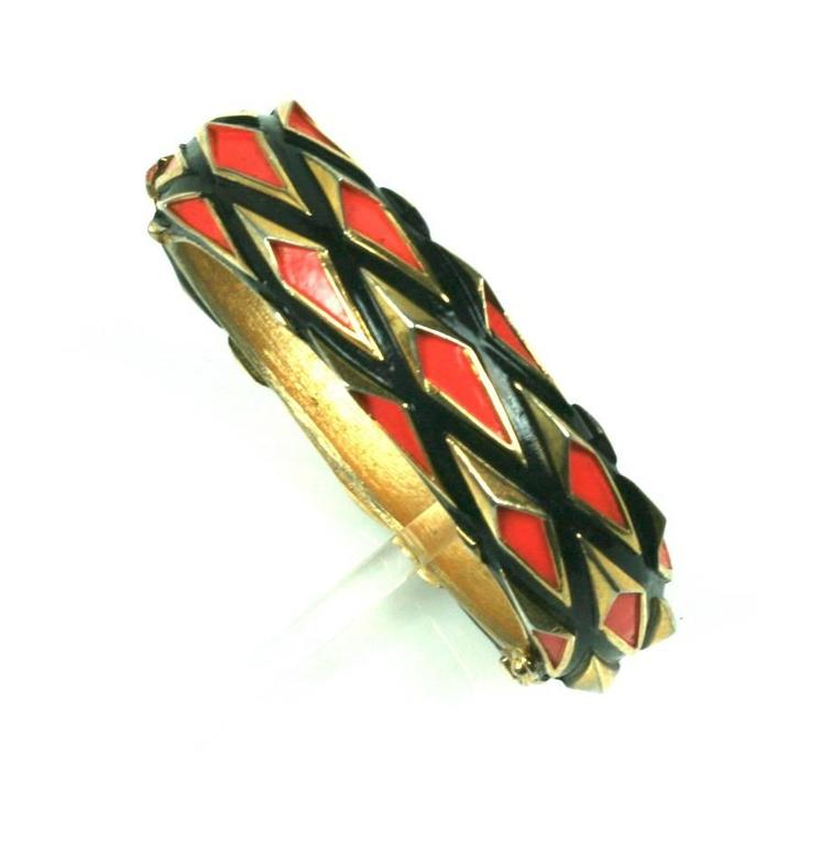 Modernist Trifari Bangle in gilt metal with orange and black enamel highlights.
