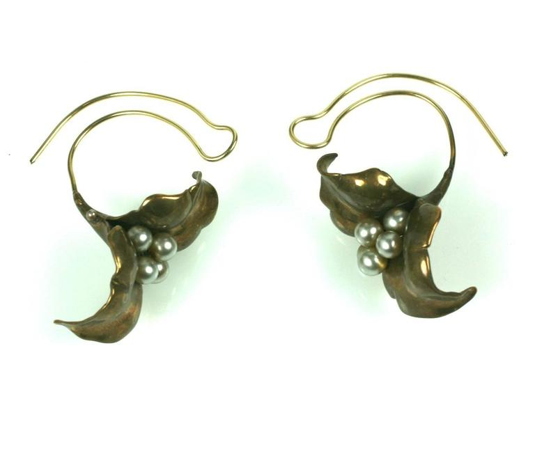 Unusual Artisan Cala Lily Earrings with faux glass pearls. The flowers hang low below the lobes and the ear wires are quite unusual as they mimic the curve of the flower stem. Handmade in brass and extremely graphic in form. Flower head measures
