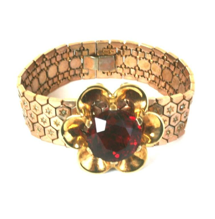 Trifari Retro Style flexible honeycombed rose gold plated and crystal pave link bracelet. Its focal large faux faceted ruby stone is prong set in a retro floriform removeable clip brooch.  A novelty jewelry design of the period. Excellent Condition.