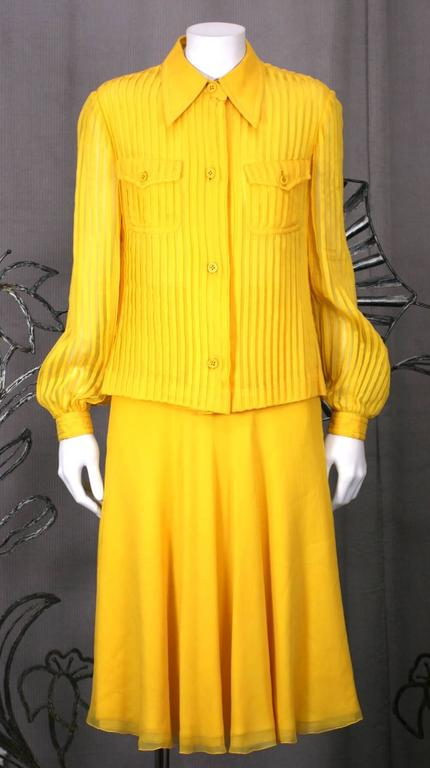 Galanos' Charming Chrome Yellow silk chiffon set with pin tucked shirt and 5 ply chiffon bias cut skirt. Blouse is completely pin tucked with 2 chest pockets and heavy silk top stitching. The top stitching is also repeated on the waist band of the