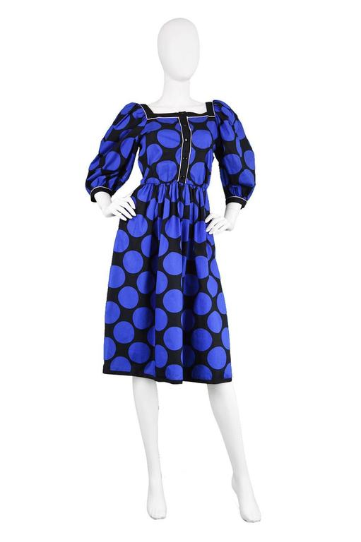 A chic vintage dress by highly regarded French designer, Louis Féraud from the 1980s, in a black and blue polka dot cotton fabric. The voluminous puff sleeves give a chic, high fashion look whilst the square neckline flaunts the wearer's