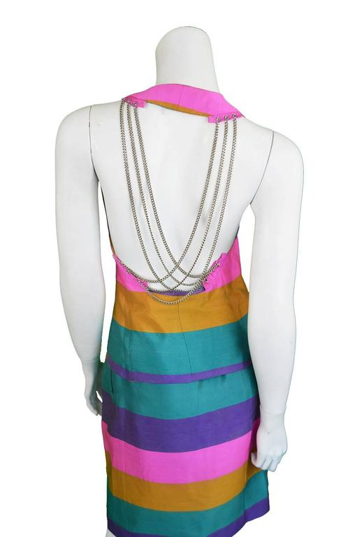 An incredible vintage womens two piece skirt suit from the 1990s by legendary French designer, Paco Rabanne. In an incredible rainbow striped silk dupion fabric with silver tone metal chains draping elegantly down the open back, creating the space