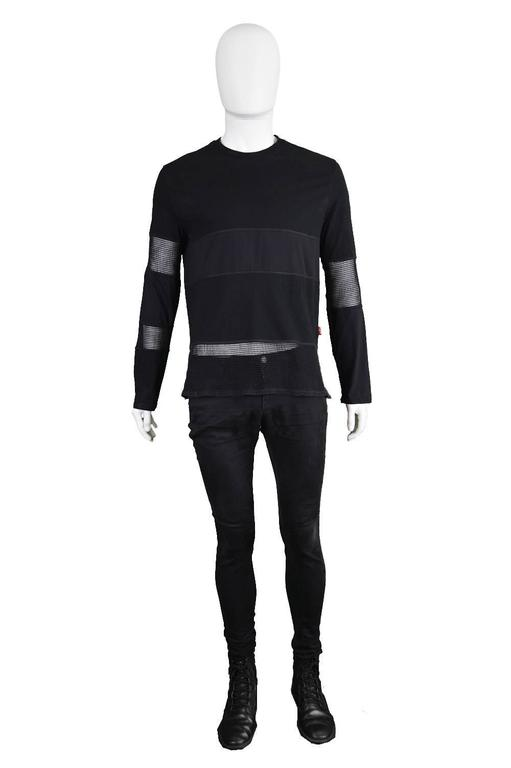 An amazing vintage Jean Paul Gaultier long sleeve t-shirt from c.the 1990s for the JPG Jean's line. In a black cotton-elastane jersey with sheer mesh panels on the arms and along the hem - which shows Gaultier's talent for creating avant garde