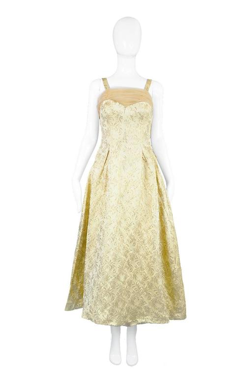 A glamorous vintage evening dress from the 50s with a ruched chiffon shelf bust and matching train to the rear. In a luxurious gold silk and lame brocade by Lee Delman.  Estimated Size: UK 8-10 / US 4-6/ EU 36-38 Bust - 32