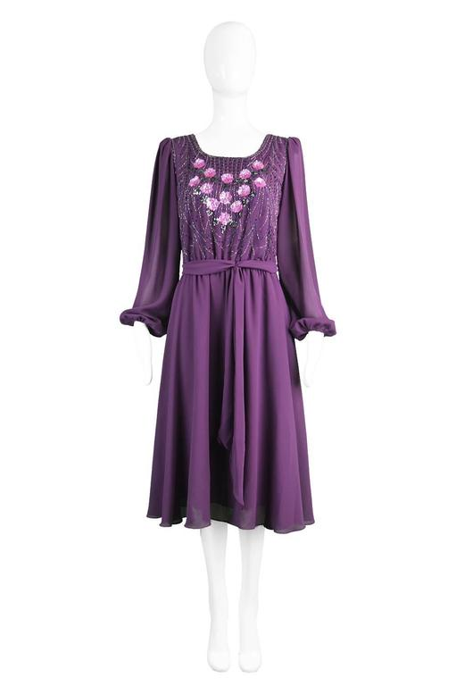 A glamorous purple vintage beaded dress from the 1970s with billowing chiffon balloon sleeves by Jack Bryan.
