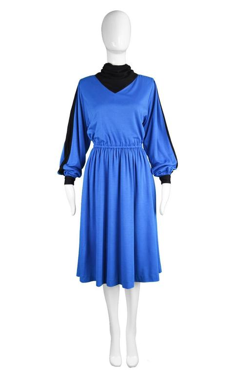 A chic vintage dress from the early 80s by luxury Swiss label, Akris. In a blue wool blend fabric with a black cowl neck and stripes down each sleeve. The top is voluminous for a casual look with an elasticated waist that creates a flattering