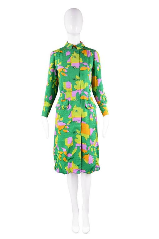 A gorgeous vintage dress by legendary American designer, James Galanos for Amelia Gray of Beverly Hills. In a fabulous green textured silk with a vibrant, tropical/ abstract print throughout. With topstitching highlighting the collar and cuffs and