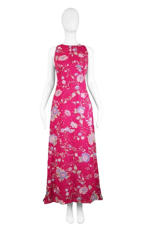 An elegant and feminine vintage maxi dress from the 1990s in a fuschia pink silk with an Asian/ Chinese style floral print throughout. Perfect for day or evening, this gorgeous sleeveless dress has a subtle keyhole at the bust to add a flash of