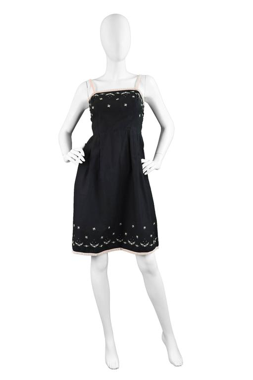A chic vintage sleeveless dress from the 60s by luxury French label, Anne Valore. Completely hand constructed in a black cotton fabric with pastel pink velvet trim and ditsy floral embroidery. It has a nipped waist and an A-line skirt making it