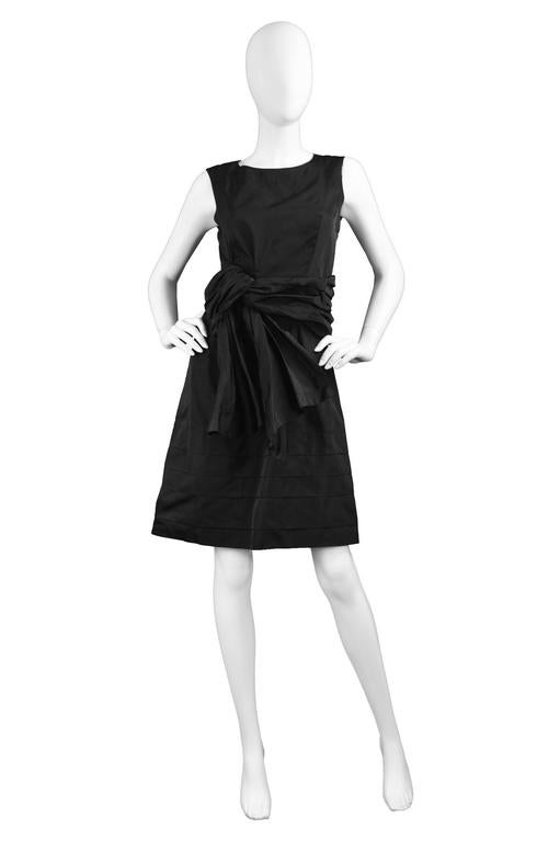 A chic sleeveless evening / party dress by Chloé. In a black 100% silk taffeta which gives incredible sheen and a tiered skirt. With a draped / soft pleated detail at the waist which looks like a nonchalantly deconstructed bow.   Size: Label states