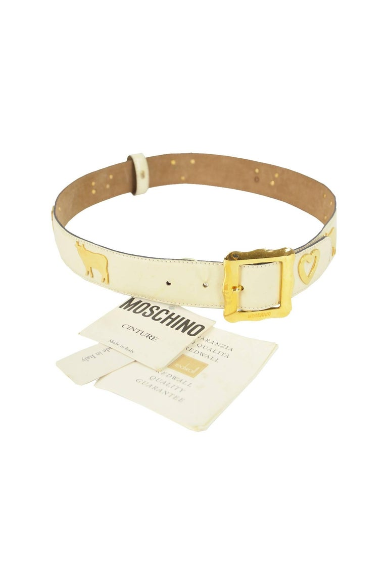 "Moschino Vintage White & Gold Leather Belt with Cows & Hearts, 1980s NWT  Estimated Size: UK 8-10/ US 4-6/ EU 36-38. Please check measurements.  Width (Smallest notch) - 26"" / 66cm Width (Largest notch) - 28"" / 71cm Length - 1.4"" / 3.5cm  Condition:"