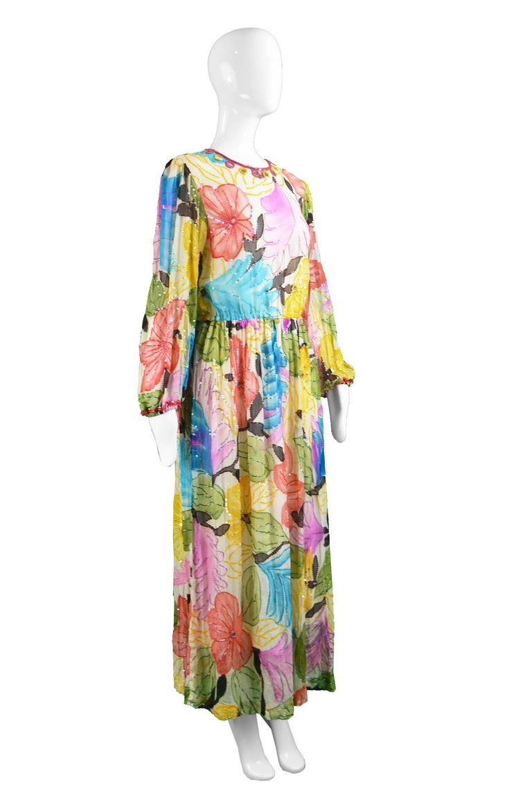 A breathtaking vintage evening dress from the 70s by New York couturier and luxury designer, Swee Lo, known for her beaded silk gowns. This stunning example has a bohemian watercolour style print with mirrorwork at the top and glass beading adding a