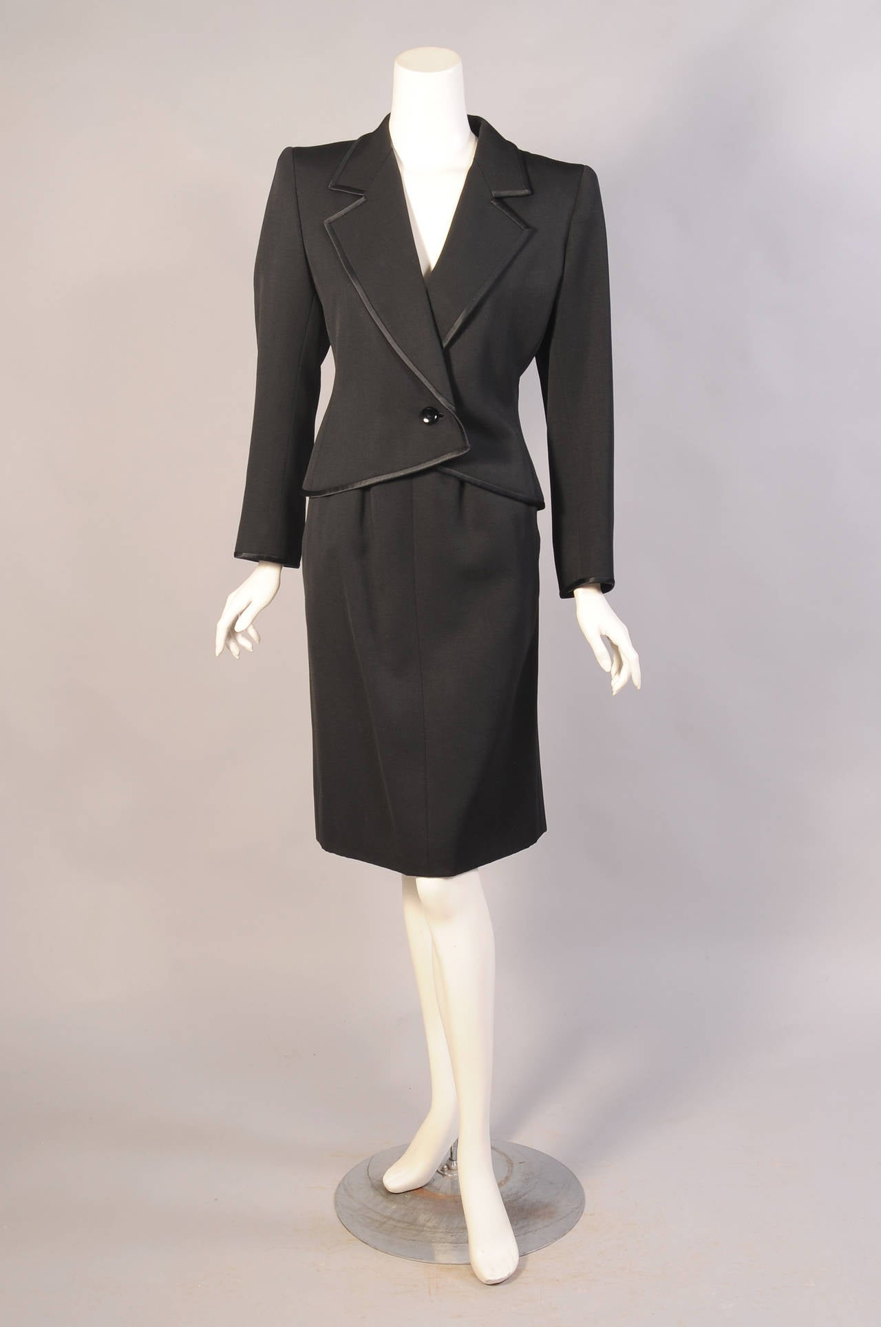 Black silk faille is accented with black silk satin on the lapels and cuffs of this one button Le Smoking suit from YSL. The straight skirt has two pockets and a left side zipper. Both pieces are fully lined in black silk and hand finished in the