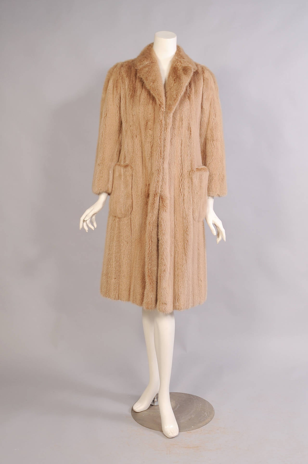"""This classic light mink coat has a notched lapel and two patch pockets. It is fully lined in matching silk and it is in excellent condition. Measurements; Shoulders 15"""" Bust 40"""" Sleeve 21.5 Length 41"""""""