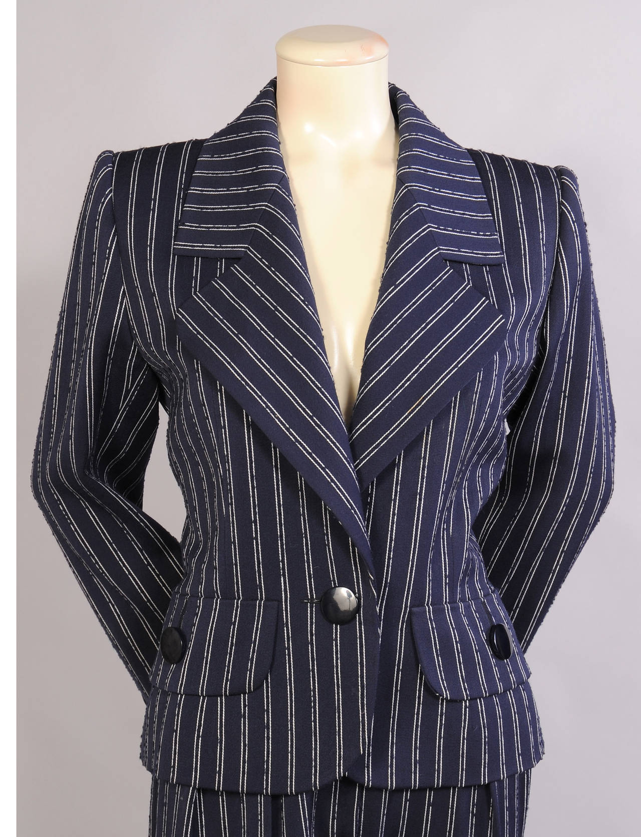 Classic navy and white broken pinstriped wool in a spring weight adds an elegant touch to this trouser suit. The jacket has notched lapels, a single button closure and two hip pockets. The pants have a natural waistline and a center front zipper.