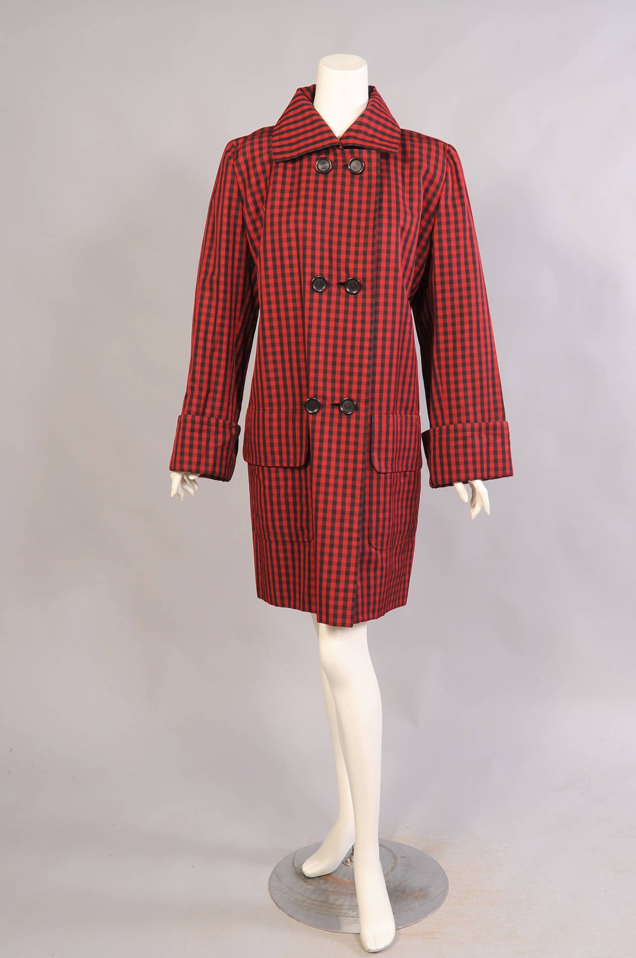 This generously cut red and black checked coat has six large black buttons, two large patch pockets and deep cuffs. The back of the coat has a deep yoke. It is fully lined in black silk and bears the numbered Givenchy Haute Couture label. It is in