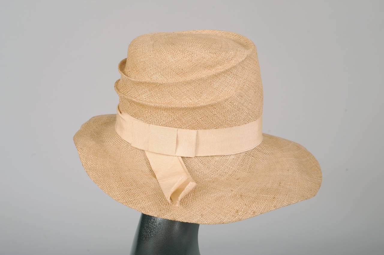 This natural straw wide brimmed cloche was recently exhibited at critically acclaimed the Neue Gallery Berlin Metropolis Show. The natural straw is folded to create a pleated look on the crown. A matching grosgrain ribbon hatband completes the look.