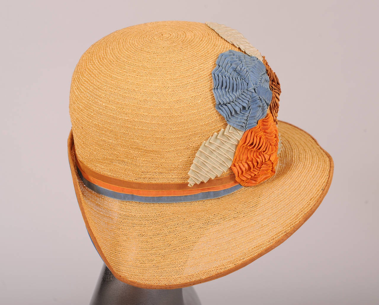This 1920's natural straw cloche is beautifully trimmed with multi color grosgrain ribbons. The hat band is three narrow ribbons, tan, coral and blue, sewn together to create a wide band. Large flowers and leaves are made from pleated and folded
