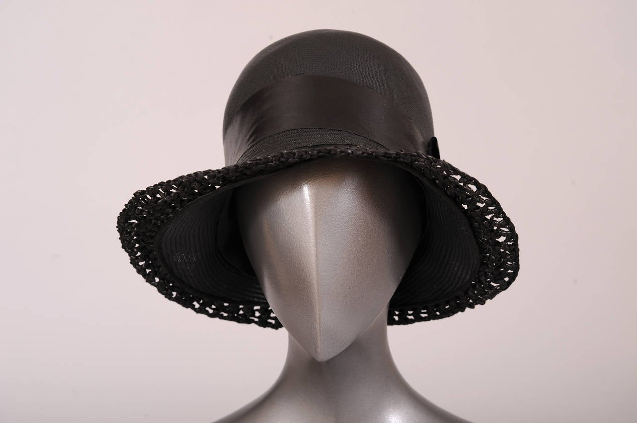 Designed by Le Chapeau Chic and retailed by Bonwit Teller in the 1920's, this hat is definitely chic. The fine black straw is trimmed with a black satin ribbon band. The brim is accented with a band of loosely woven raffia. The hat has a very