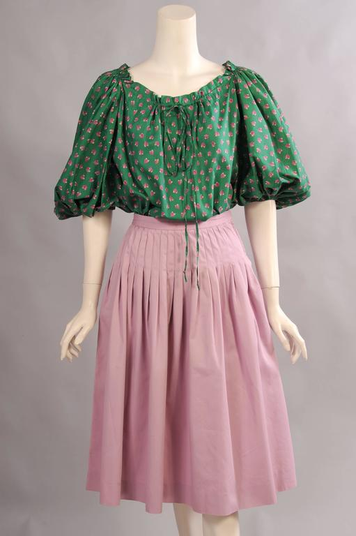 A bright green peasant style cotton blouse with a lavender floral design has a gathered drawstring neckline and full sleeves with elastic. The coordinating lavender cotton skirt has a natural waistline, stitched down pleats and two pockets concealed