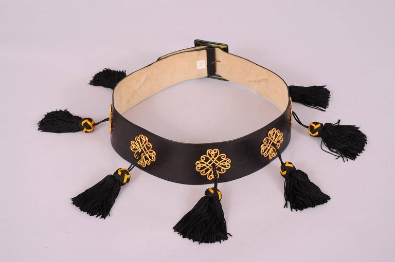 A classic wide black leather belt, curved to fit the waistline, is beautifully embellished by Isabel Canovas. The belt has a leather covered buckle and seven gold toned scrolling medallions. Each of these medallions suspends a black and gold topped