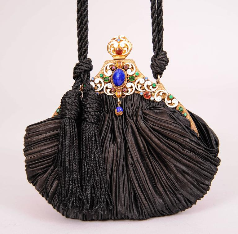 This elegant jewel frame dates to the 1930's and it is set with a large lapis stone at the center surrounded by a white enamel frame and multi color faceted stones. The body of the bag dates from the 1980's and it is black pleated silk. There is a