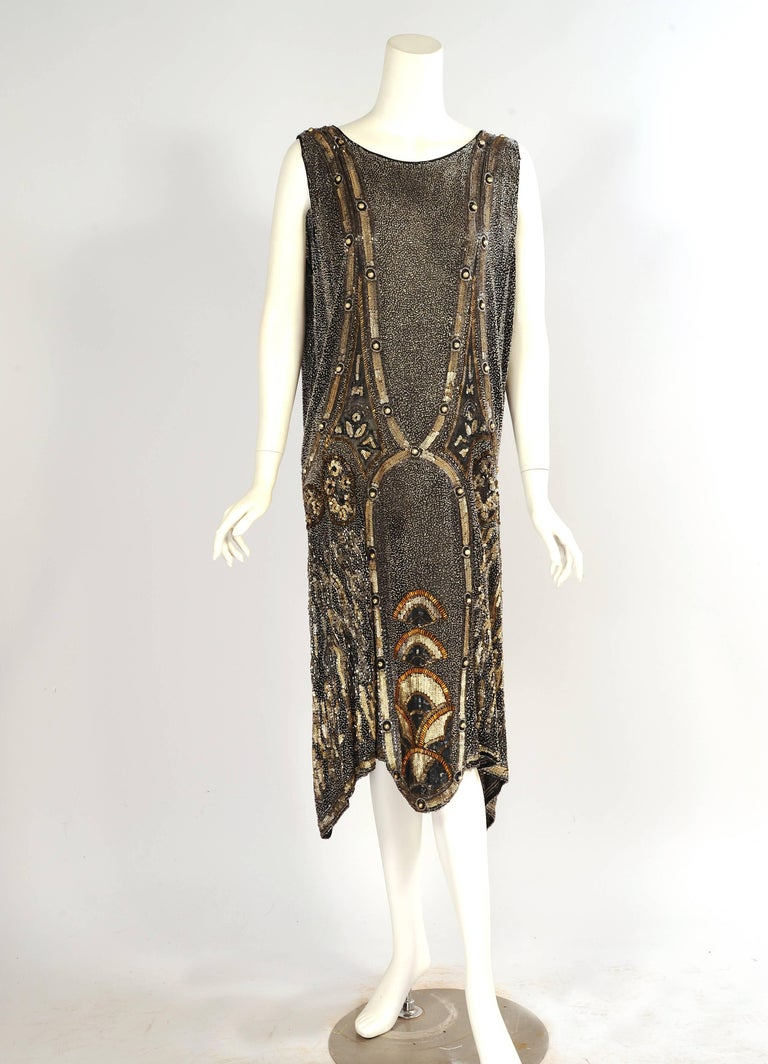 This stunning Art Deco flapper dress is is completely beaded. The body of the black cotton dress is covered with tiny clear beads. Silver bugle beads outline the graphic design which is made with textured matte gold sequins and gold blister pearls.