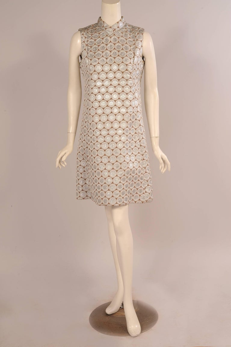 This sleek 1960's sheath dress has a cafe au lait background color covered with Op Art silver circles for a very  festive look. There is a half belt at the back with rhinestone studded cafe au lait buttons on either side. The dress was designed by