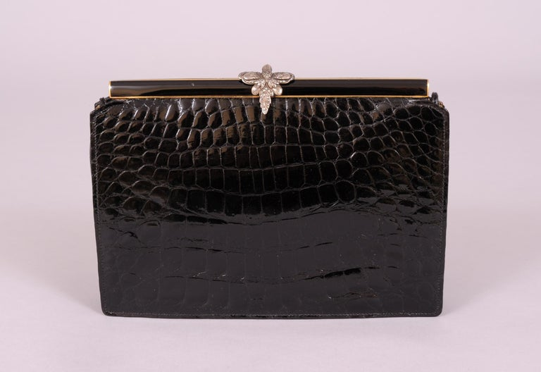 This stunning black crocodile evening bag is topped with a marcasite  set sterling silver clasp. The frame is black enamel over gold toned metal, front and back. The black crocodile skin is in pristine condition, as is the convertible handle. The