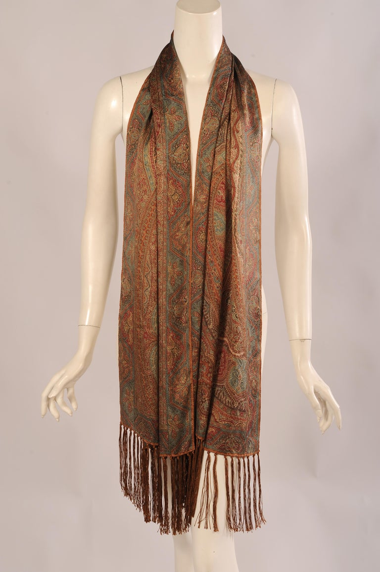 A subtle palette is used for this paisley patterned silk shawl in muted shades of rust, brown, cream, red and blue. The rectangular scarf has brown silk fringe at each end. It is in excellent condition and comes with the original